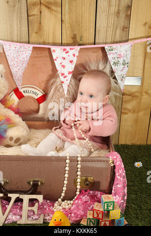 pretty baby girl sitting in suitcase playing with toys in the garden - Stock Photo