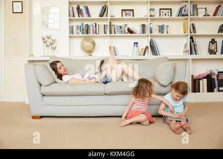 Pregnant woman reclining on sofa with smartphone and daughters sitting on floor drawing - Stock Photo