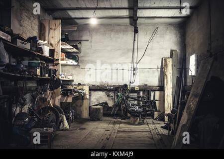 Mechanic sitting in armchair looking at dismantled vintage motorcycle in workshop - Stock Photo