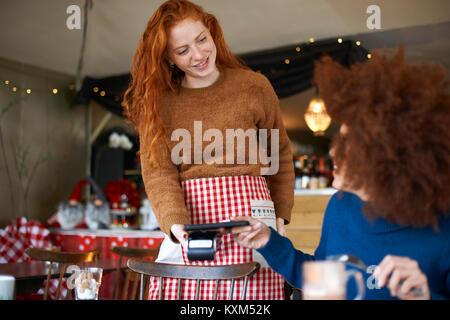 Customer in cafe making contactless payment with mobile phone - Stock Photo