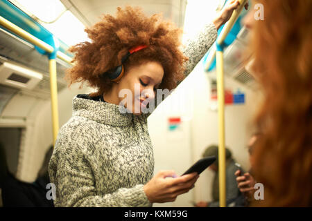 Young woman on subway train,looking at smartphone - Stock Photo