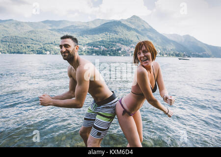 Portrait of couple in swimwear buttock to buttock in Lake Como,Lombardy,Italy - Stock Photo
