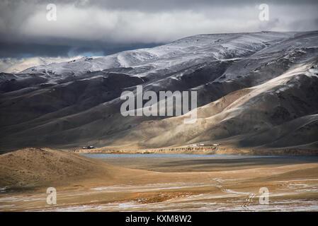 Mongolian landscape snowy mountains snow winter cloudy Mongolia - Stock Photo