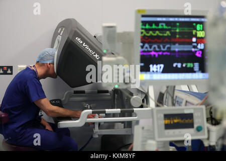 The Duke of Cambridge looks through a dual console of the da Vinci robot while lead surgeon Vin Paleri (out of frame) - Stock Photo