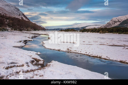 UK winter landscape: Stunning view down the stream at the mouth of Loch Broom with snowy mountains and snow-covered - Stock Photo