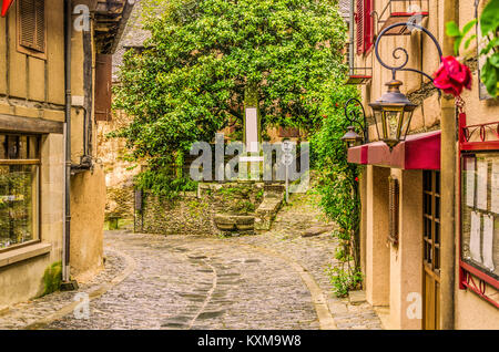 Crossing of narrow streets and monolith to the fallen ones in the war in the old medieval village of Conques on - Stock Photo