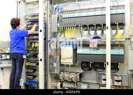 production and assembly of microelectronics in a hi-tech factory - older woman assembles components - Stock Photo