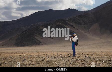 Woman taking pictures golden eagle hunter Kazakh eagle festival tourist Bayan Ölgii Ulgii - Stock Photo