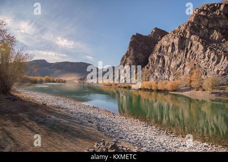 Green river bank yellow leafs fall golden hour calm stream river reflections cliffs Mongolia - Stock Photo