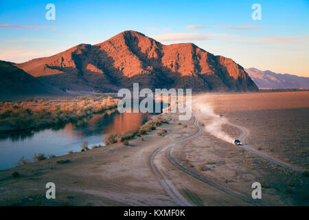 Dirt road cars racing dust cloud sunset landscape Mongolia red mountain river reflection - Stock Photo