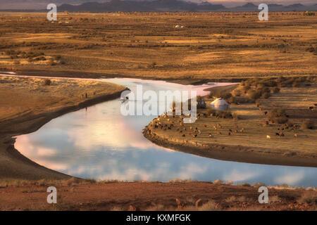 Sunset horse crossing river Mongolia landscape plains grasslands steppes goats herd ger golden hour - Stock Photo