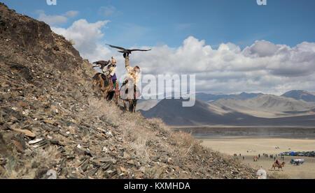 Golden eagle hunter father and eagle huntress daughter Mongolia Mongolian Ulgii Ölgii eagle festival - Stock Photo