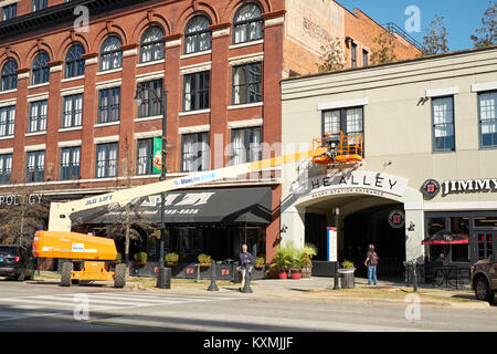 JLG telescopic boom lift in use while a worker performs maintenance on a building window in downtown Montgomery - Stock Photo