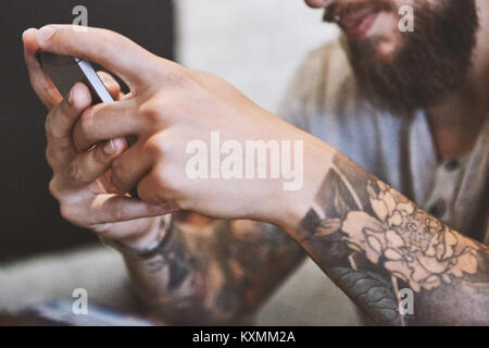 Hands of tattooed young male hipster holding smartphone,close up - Stock Photo