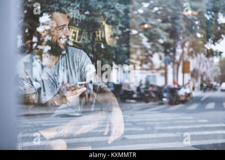 Young male hipster in cafe window seat holding smartphone,Shanghai French Concession,Shanghai,China - Stock Photo