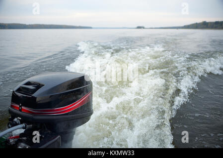 Motor boat trail in calm river waters on a autumn day - Stock Photo