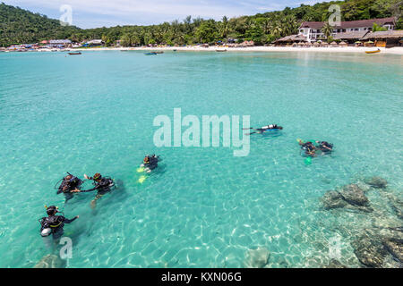 A group of Scuba Diving students have a lesson in the shallow crystal clear water of a Tropical Island. - Stock Photo