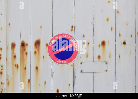 Old wooden garage door with no parking sign in French - Stock Photo