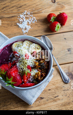Acai bowl with spoon and ingredients - Bowl of acai purée with toppings of banana, strawberry, granola and seeds. - Stock Photo