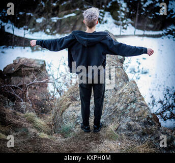 Young man on cliff edge - Stock Photo