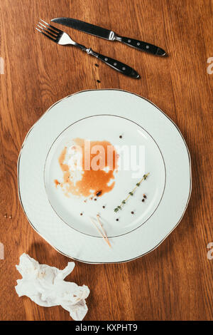 remainings of meat in almost empty plate on wooden surface with fork, knife and wrinkled napkin - Stock Photo