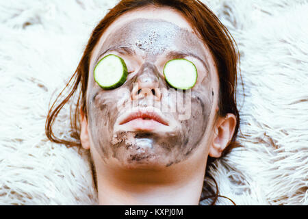 Redhead model using an exfoliant, black coal mask to peel off and cucumber slices for the dark circles - Stock Photo