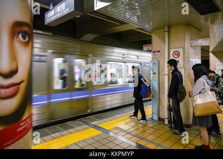 NAGOYA, JAPAN - NOVEMBER 18, 2015: Unidentified Japanese commuters wait for an underground train in Nagoya Underground system Stock Photo