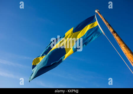 Swedish flag blowing in the wind against clear blue sky, Stockholm, Sweden - Stock Photo