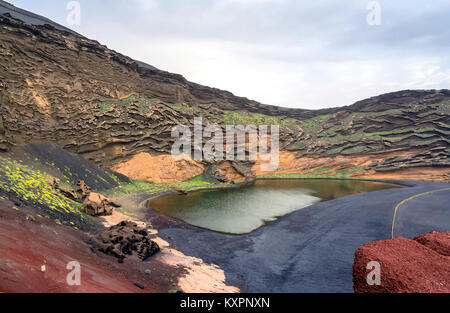 green lagoon on the Atlantic Ocean in El Golfo village, Lanzarote. A rocky beach with fishing boats surrounded by - Stock Photo