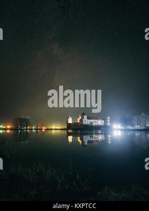 Scenic view of Mir Castle Complex in night with starry sky and glow reflexion on lake. Landmark in Belarus - Stock Photo