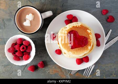 Pancakes with jam in shape of heart, hot chocolate and raspberries over a slate background. Love concept. - Stock Photo