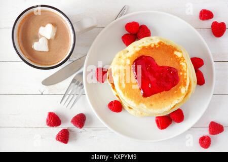 Pancakes with jam in shape of heart and hot chocolate with marshmallow hearts over a white wood table. Love concept. - Stock Photo