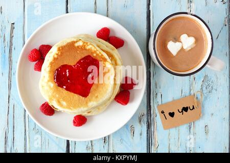 Pancakes with jam in shape of heart, hot chocolate and I Love You git tag over a blue wood table. Love concept. - Stock Photo