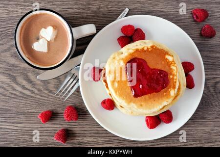 Pancakes with jam in shape of heart, hot chocolate and raspberries over a wood background. Love concept. - Stock Photo