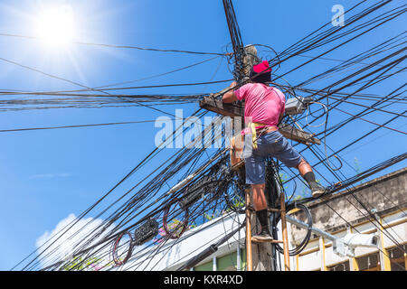 no safety worker technician installing Internet cables on the electricity poles in asian country - Stock Photo