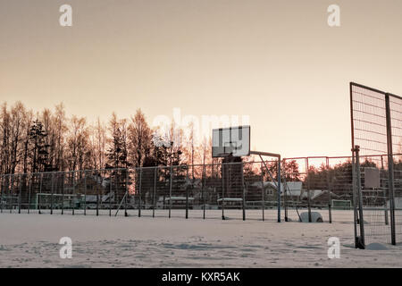 The town basketball field is covered with heavy snow at the rural town of Oulainen, Finland. The sun is setting - Stock Photo