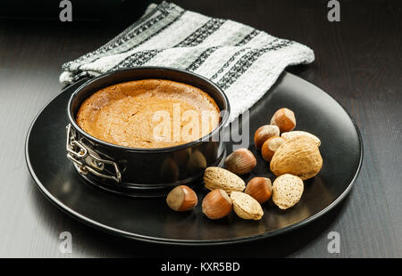 Homemade chocolate cheesecake in small springform pan on black plate with nuts on the table. - Stock Photo
