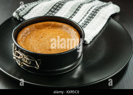 Homemade chocolate cheesecake in small springform pan on black plate on the table. - Stock Photo