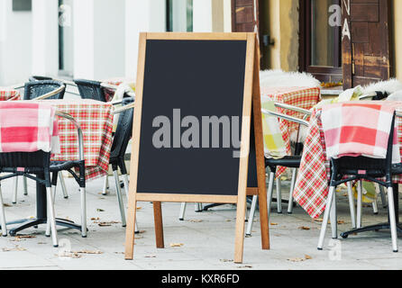 Blank menu chalkboard mockup on the street with empty cafe seats - Stock Photo