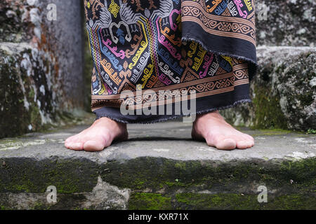 Close up view on man foot in balinese indonesian sarong. - Stock Photo