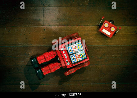 retro red robot has lost his head on a old wooden floor from above - Stock Photo