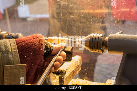 The Tool wood Handle Making Process. The hands of the craftsman who work the wood with the small lathe. - Stock Photo