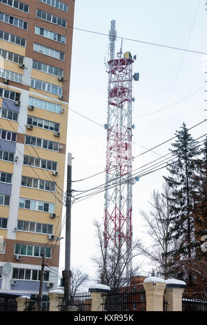 Transmission TV antenna next to an apartment building - Stock Photo