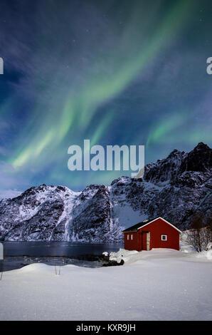 Lofoten, Svolvaer, Aurora Borealis over a frozen lake and red rorbu, Norway. - Stock Photo