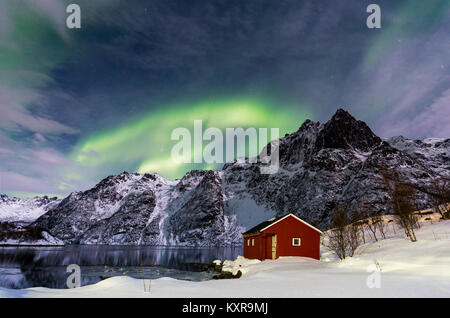 Lofoten, Svolvaer, Aurora Borealis over a frozen lake and red rorbu, Norway. - Stock Photo