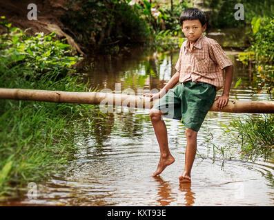 Little boy relaxing in a pond after school in Yangon, Myanmar - Stock Photo