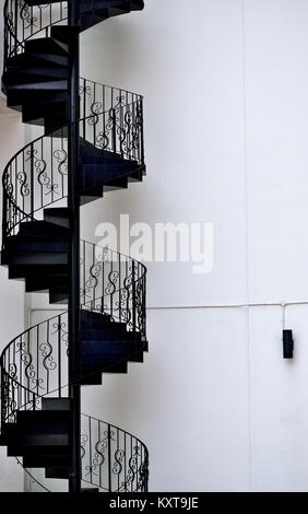 Intricate antique iron spiral staircase on the exterior of a house in Singapore - Stock Photo