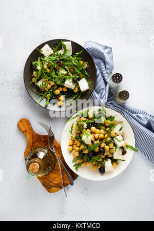 two plates of vegetable salad with chickpeas, arugula, feta cheese or tofu and black olives on a natural stone background. - Stock Photo