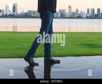 A man wearing boots walking through a puddle - Stock Photo