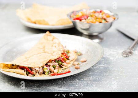 Savoury Buckwheat Pancake with White Beans, Red and Yellow Bell Pepper, Parsley and Chicken. Mexican Quesadilla. - Stock Photo